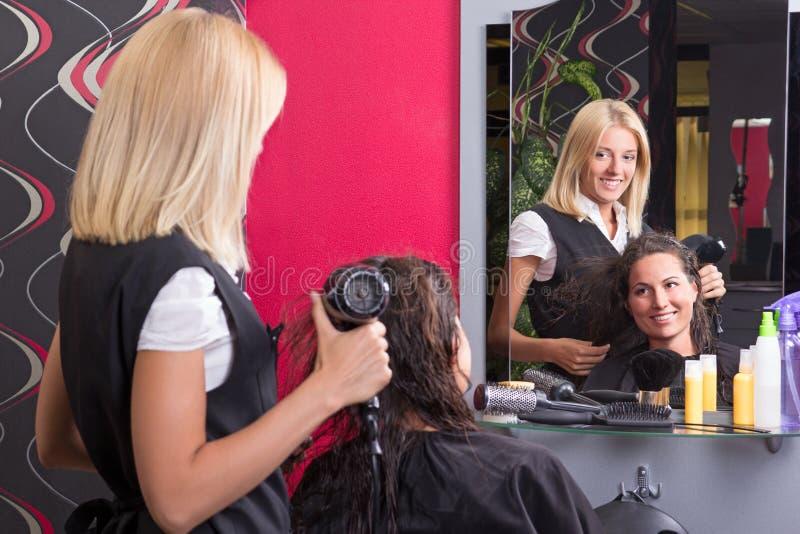 有hairdryer的年轻美发师和秀丽的微笑的顾客 免版税图库摄影