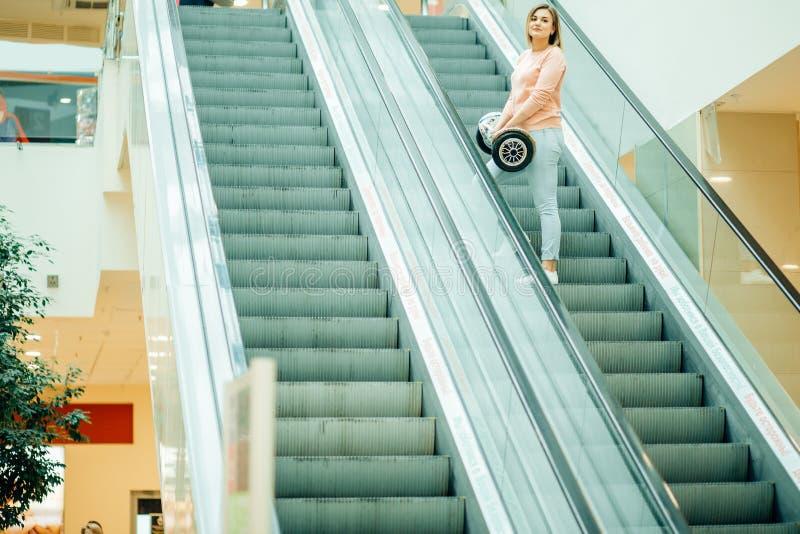 有hoverboard乘驾的女孩在自动扶梯 免版税库存照片