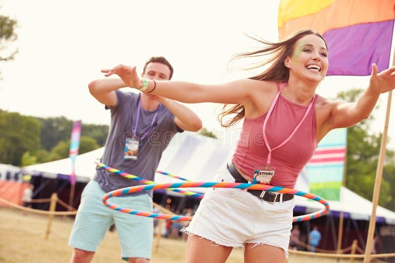 有hula箍的妇女在音乐节,人在背景中 免版税库存照片
