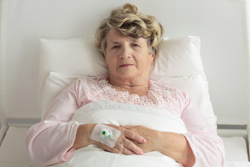 有IV滴水的老妇人 免版税库存图片