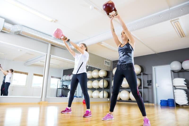 有kettlebells的两列妇女火车在健身健身房 免版税库存照片