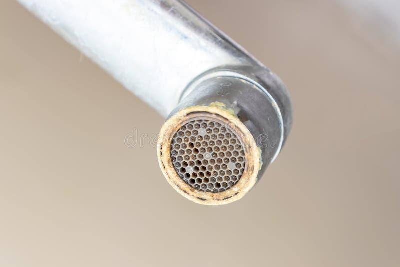 有limescale的,与石灰按比例提高的钙化的阵雨水龙头肮脏的龙头充气器在卫生间,关闭里 库存照片