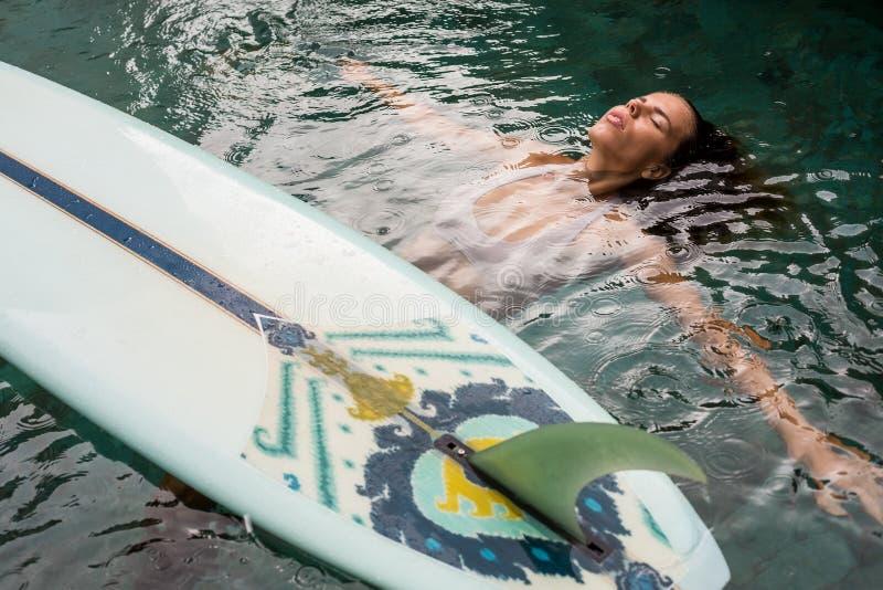 有longboard的冲浪者女孩在水池 图库摄影