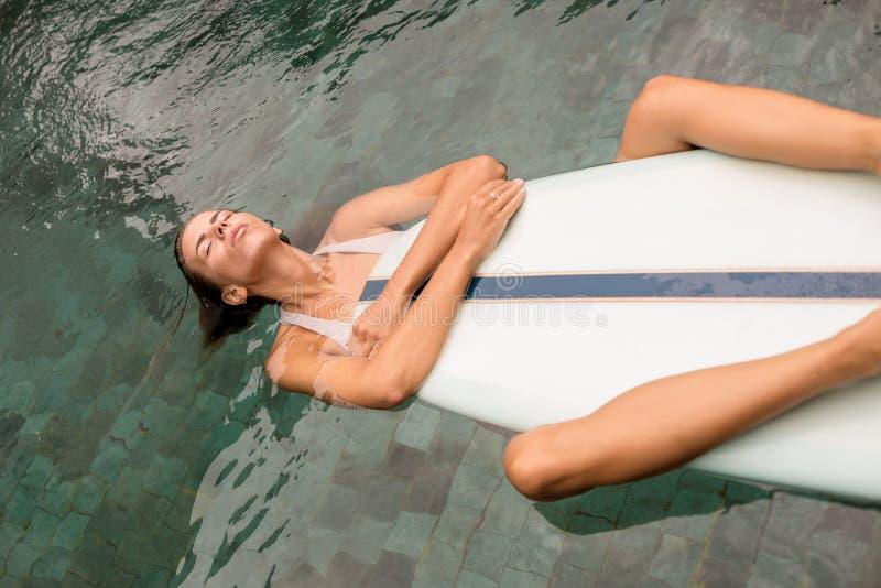 有longboard的冲浪者女孩在水池 免版税图库摄影