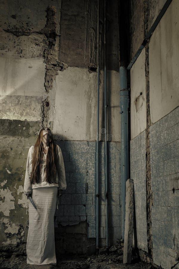 有loong头发藏品刀子的僵死女孩 免版税图库摄影