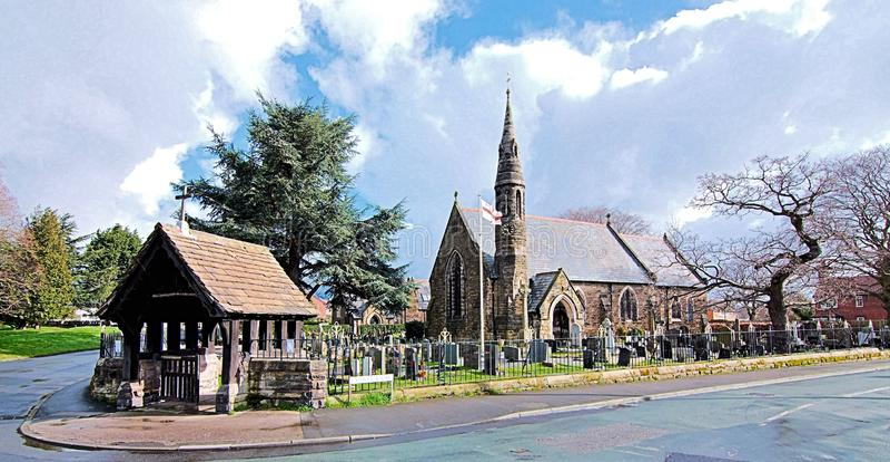 有Lychgate的一个Spired村庄教会在英国英国 图库摄影