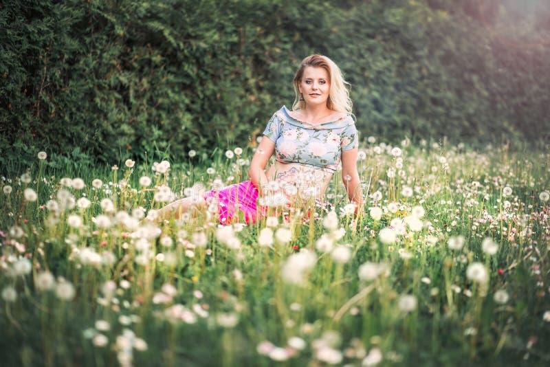 有mehendi样式的孕妇在她的腹部坐领域用蒲公英 图库摄影