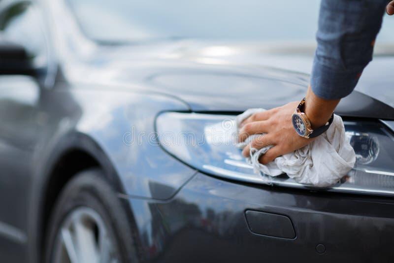有microfiber布料的一辆人清洁汽车在buing,汽车详述的或valeting的概念前 免版税库存照片
