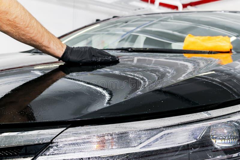 有microfiber布料,汽车详述的或valeting的概念的一辆人清洁汽车 选择聚焦 汽车详述 清洗与spong 库存照片