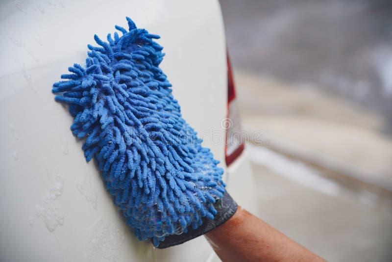有microfiber布料,汽车详述的或valeting的概念的一辆人清洁汽车 免版税库存图片