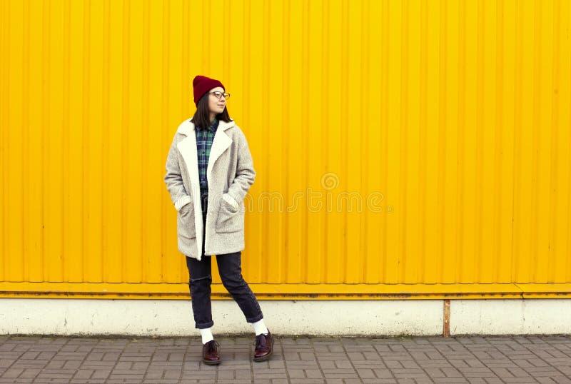 有Millenial女孩im的流行的服装好时光,做滑稽的面孔在明亮的黄色都市墙壁附近 免版税库存图片