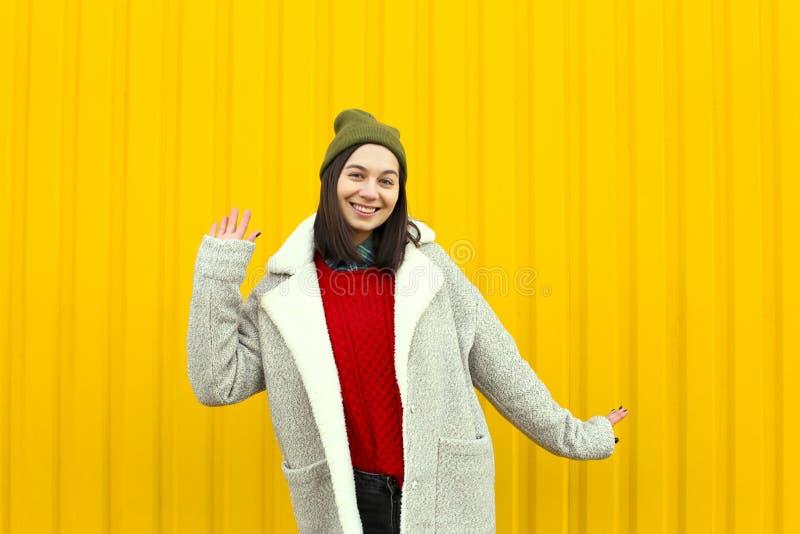 有Millenial女孩im的流行的服装好时光,做滑稽的面孔在明亮的黄色都市墙壁附近 免版税库存照片