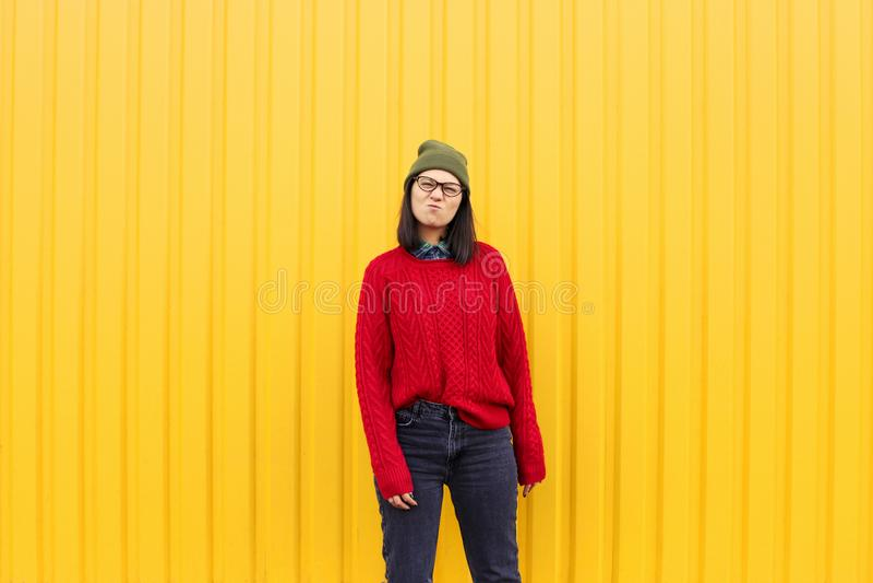 有Millenial女孩im的流行的服装好时光,做滑稽的面孔在明亮的黄色都市墙壁附近 库存图片