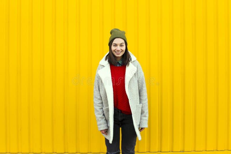 有Millenial女孩im的流行的服装好时光,做滑稽的面孔在明亮的黄色都市墙壁附近 库存照片