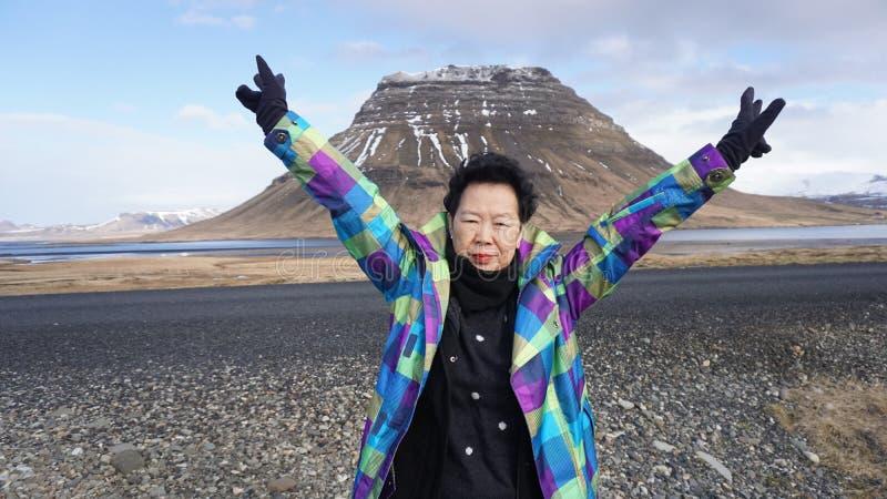 有moutain lceland地标的愉快的亚裔资深妇女 图库摄影
