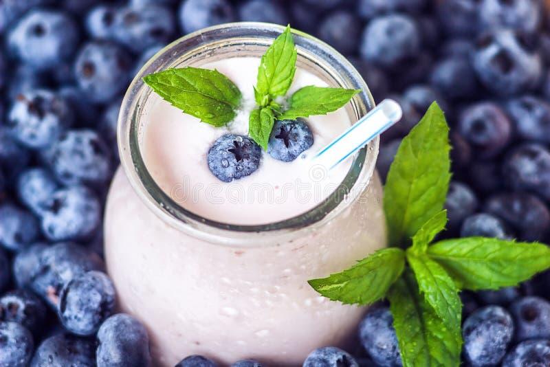 有nat水多的新鲜的莓果背景顶视图酸奶的鸡尾酒的美丽的开胃菜蓝莓果子圆滑的人奶昔玻璃瓶子 免版税图库摄影