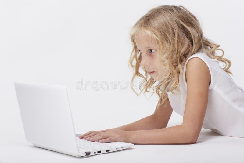 有netbook的,白色背景美丽的白肤金发的小女孩 库存图片