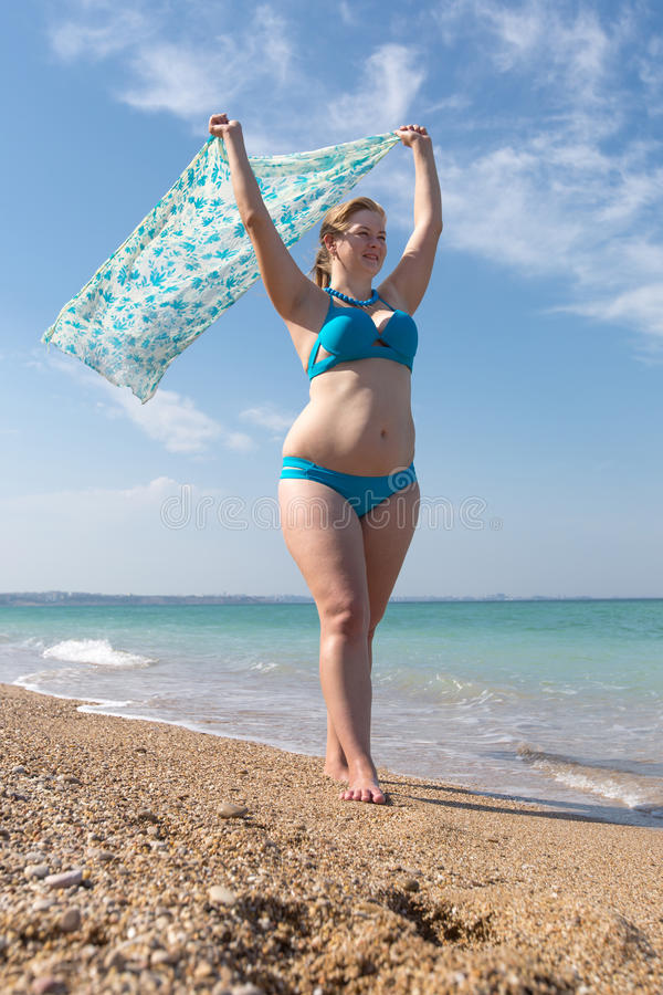 有pareo的超重中年妇女沿海滨走 库存照片