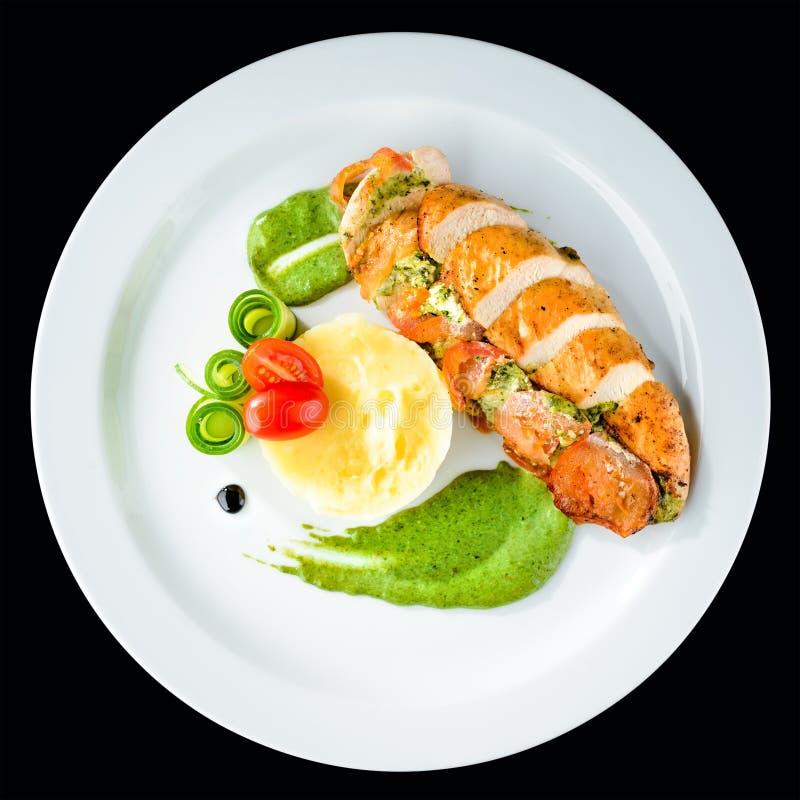 有pesto、菠菜和调味汁的烤鸡内圆角在白色 免版税库存图片