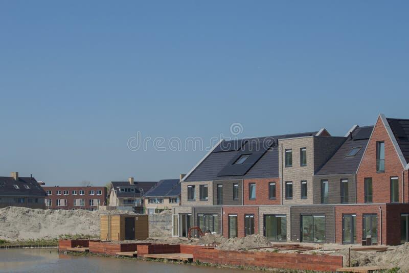 有photovoltaics的新的修造房子在屋顶在一个夏日 库存照片