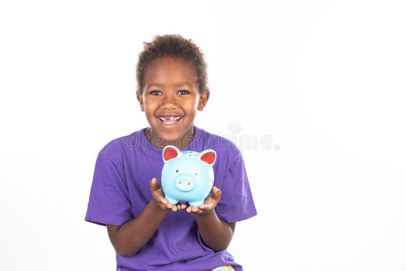 有piggybank的滑稽的非洲孩子 库存照片