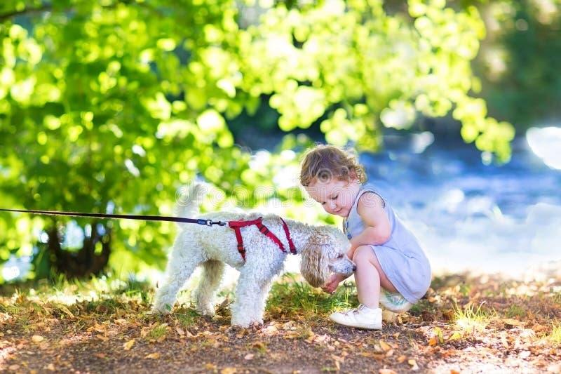 有pudel狗的可爱的女婴在河岸 免版税库存图片