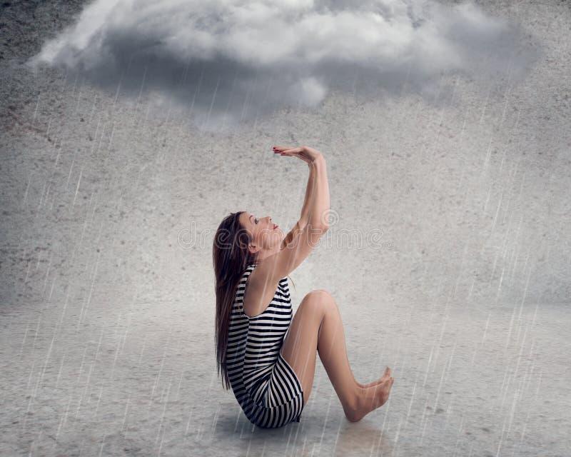 有raincloud的失望的年轻女实业家在她的头上 库存照片
