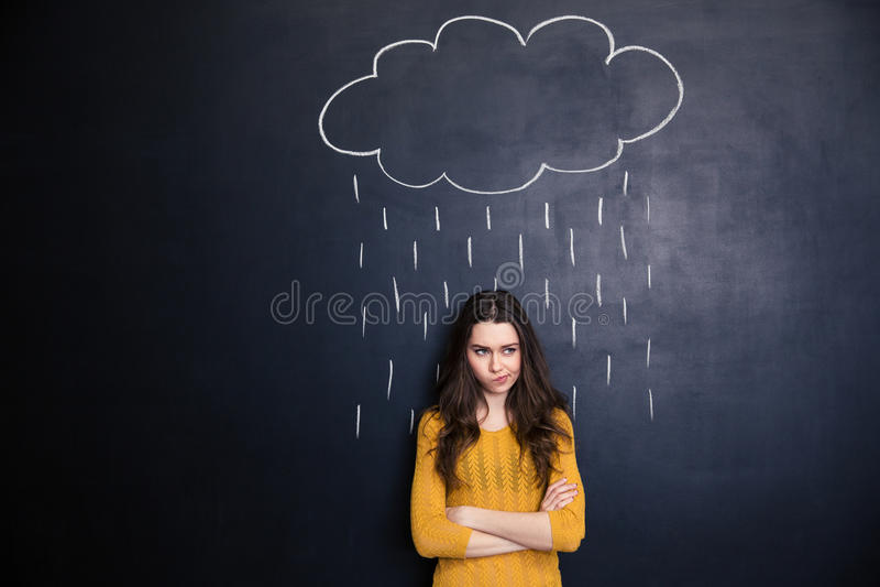 有raincloud的Unpleased妇女被画在她在黑板背景 库存图片