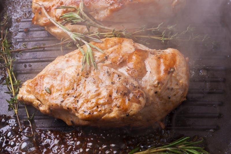 有rosmarin的烤在格栅平底锅的鸡胸脯和蒸汽 免版税库存照片