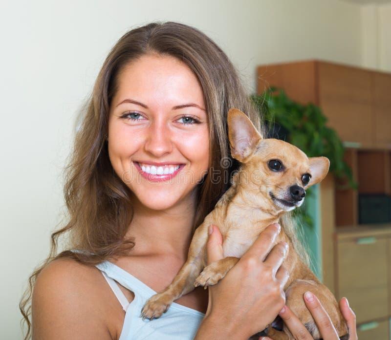 有Russkiy玩具狗的微笑的女孩 图库摄影