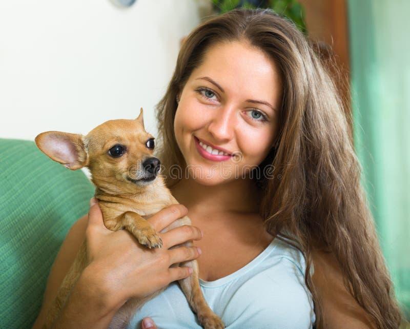 有Russkiy玩具狗的微笑的女孩 免版税库存照片