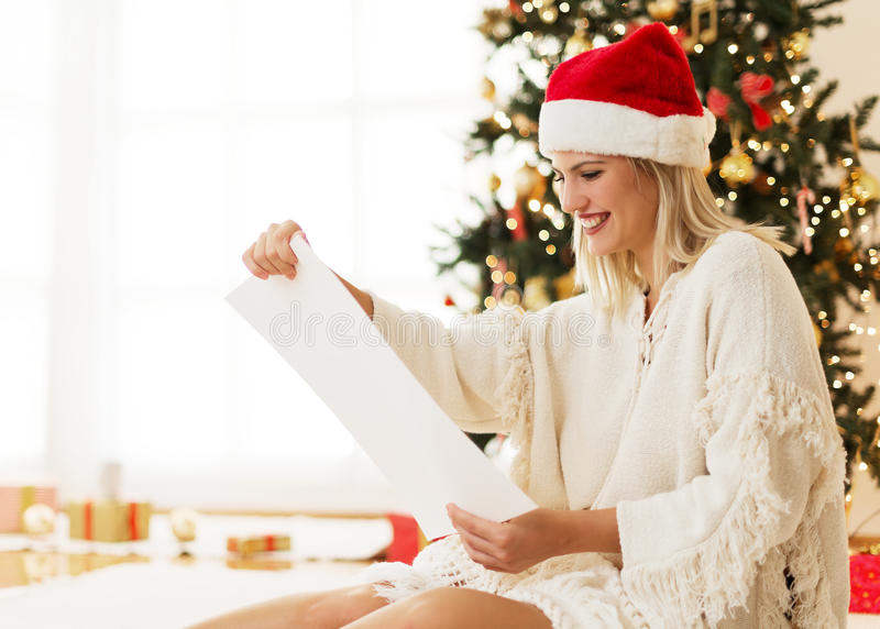 有Santa&的x27逗人喜爱,少妇; s从名单的帽子读书 免版税库存照片