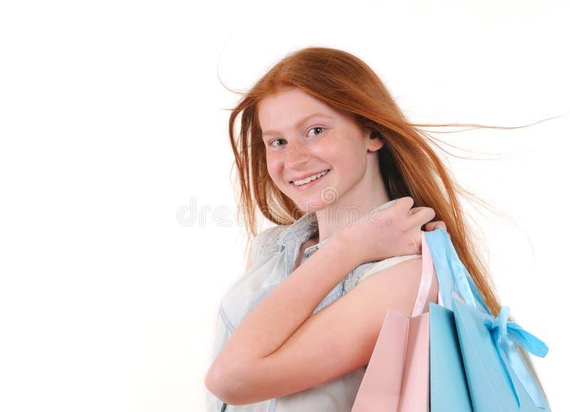 有shoping的袋子的美丽的年轻redhair妇女 免版税库存照片