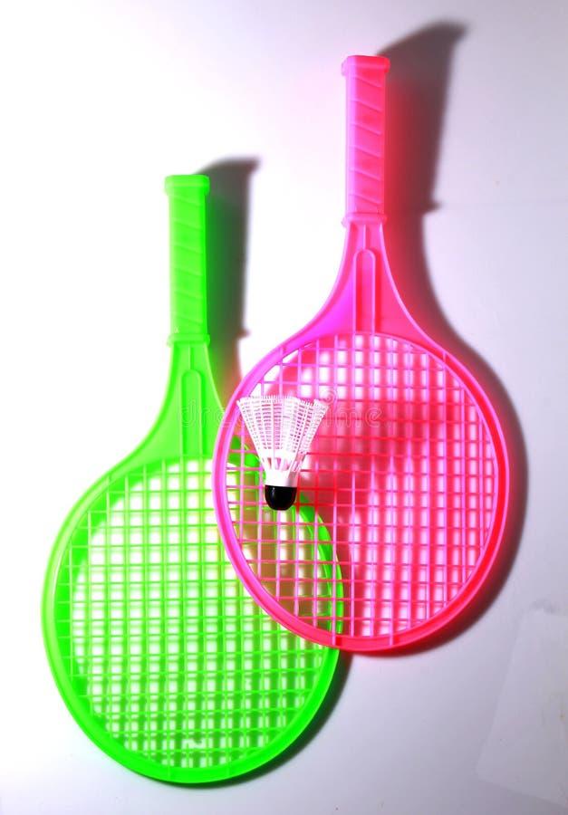有shuttlecock球的绿色和桃红色玩具球拍 图库摄影