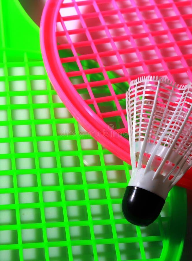 有shuttlecock球的绿色和桃红色玩具球拍 库存照片