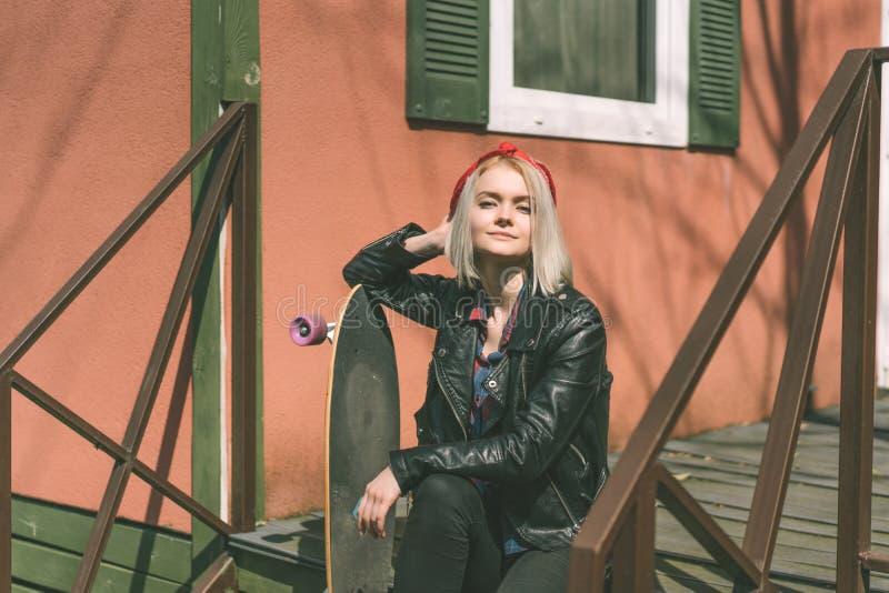 有skeatboard的时兴的都市金发碧眼的女人 免版税库存图片