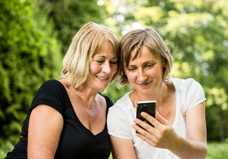 有smartphone的高级母亲和女儿 库存照片