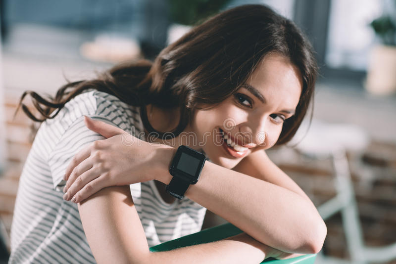 有smartwatch的微笑的妇女在腕子 免版税图库摄影