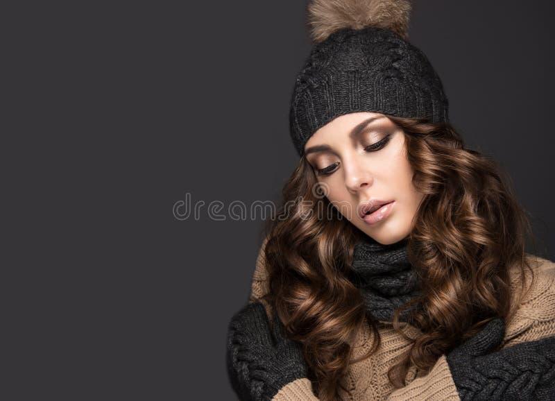 有Smokeymakeup的美丽的女孩,在黑编织帽子的卷毛 温暖的冬天图象 秀丽表面 免版税库存照片