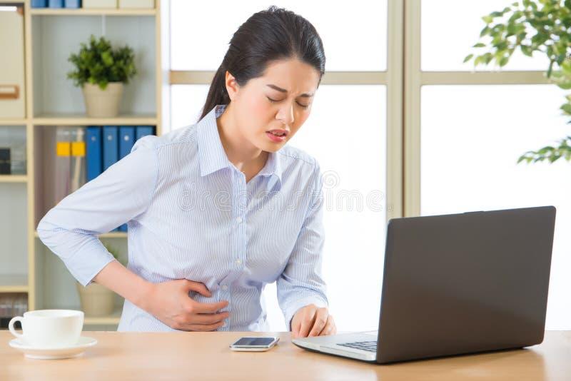 有stomachache的年轻亚裔女商人 库存图片
