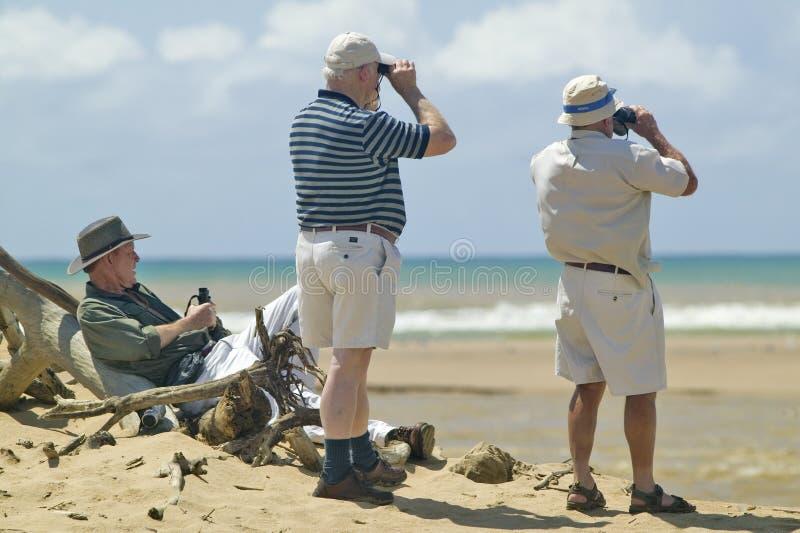 有studing鸟类的双筒望远镜的三个游人在更加伟大的圣卢西亚沼泽地公园世界遗产名录站点,圣卢西亚,南非 免版税图库摄影
