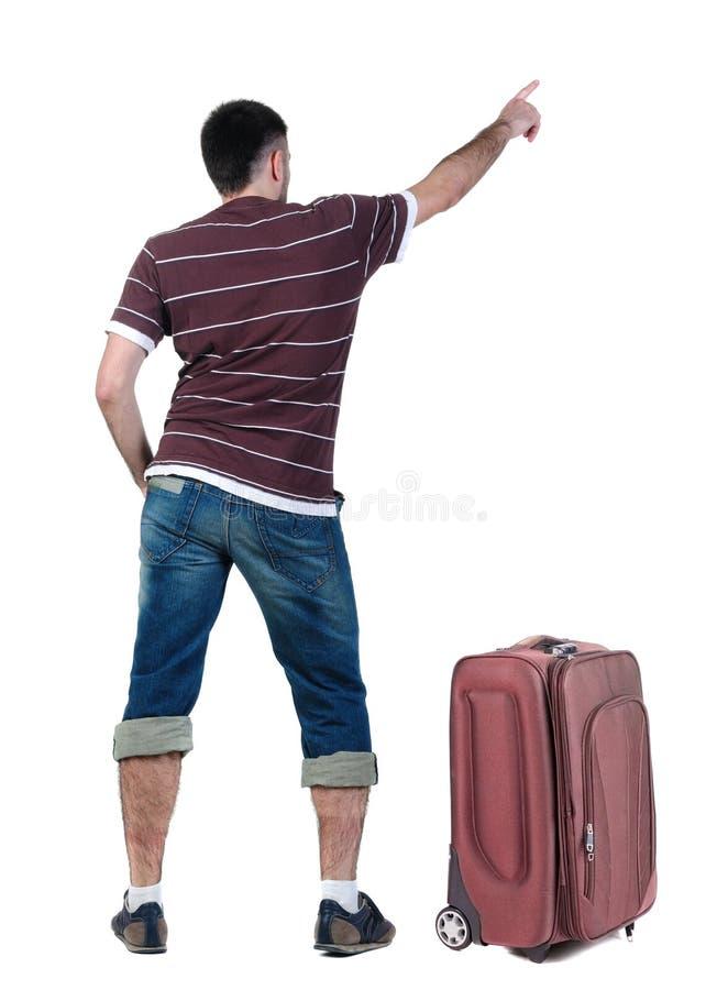 有suitcas的旅行的年轻人指向墙壁的 图库摄影
