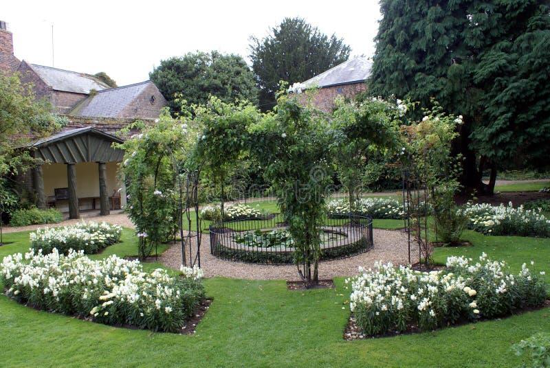 有summerhouse、百合池塘&玫瑰色曲拱的正式沉园 免版税库存图片