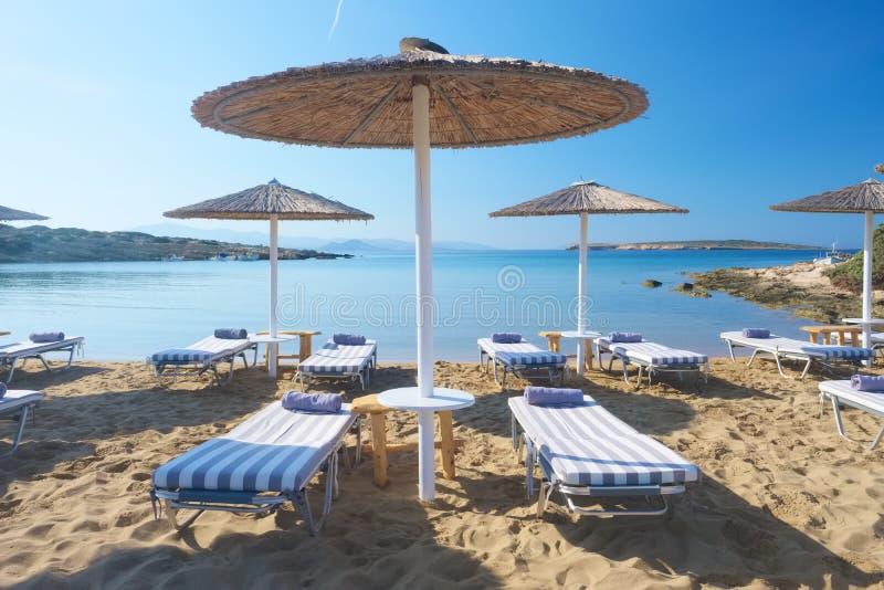 有sunbeds的伞在与绿松石海水的美丽的沙滩 免版税库存图片