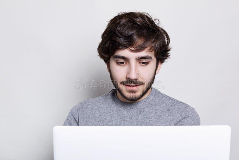 有sylish发型的可爱的有胡子的人穿灰色毛线衣花费业余时间的使用他的膝上型计算机 青年人enj的概念 库存图片
