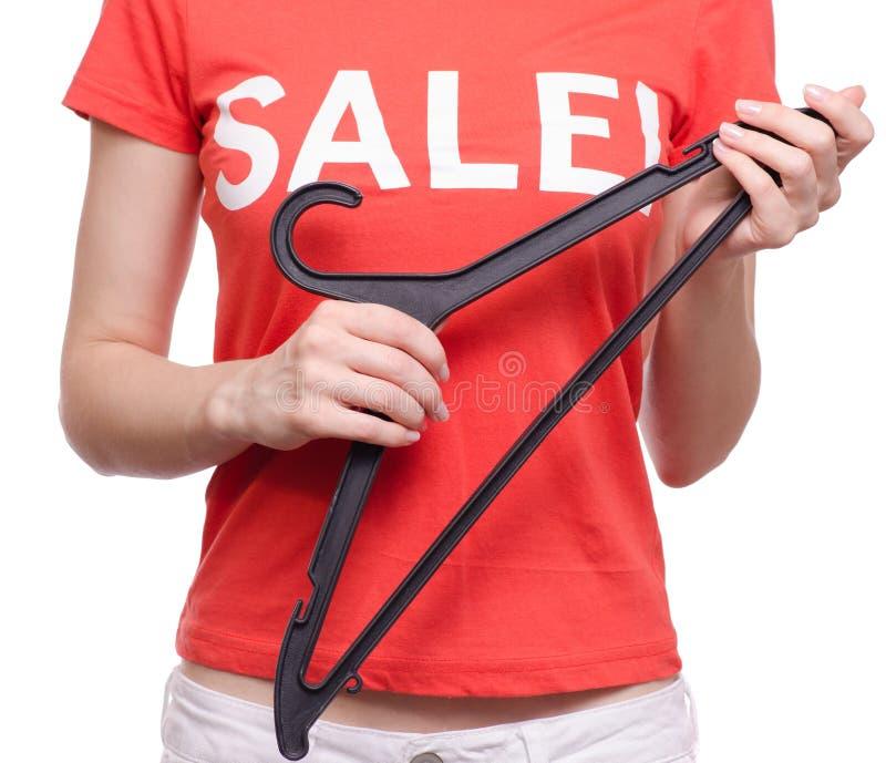 有T恤杉的妇女有题字销售手中挂衣架商店购买折扣的 免版税库存照片