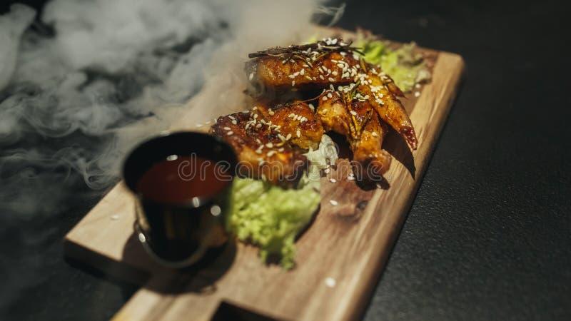 有teriyaki的炸鸡腿调味芝麻籽和米在黑石头 关闭 黑色背景 库存图片