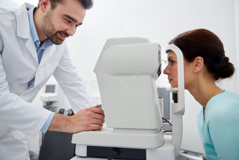 有tonometer的眼科的眼镜师和患者 免版税库存图片