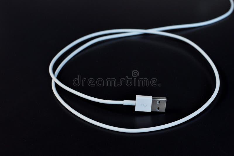 有USB的白色数据缆绳连接器在黑背景 库存照片