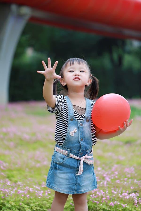 有V姿势戏剧的艾萨逗人喜爱的淘气可爱的儿童女孩与气球获得室外的乐趣在夏天公园愉快的微笑幸福童年 免版税库存图片